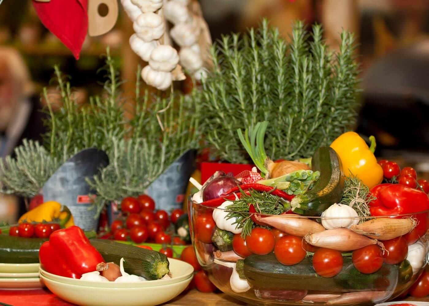 Buntes, mediterranes Gemüse in verschiedenen Behältern auf Tisch. Vegane Lebensmittel und Kräuter