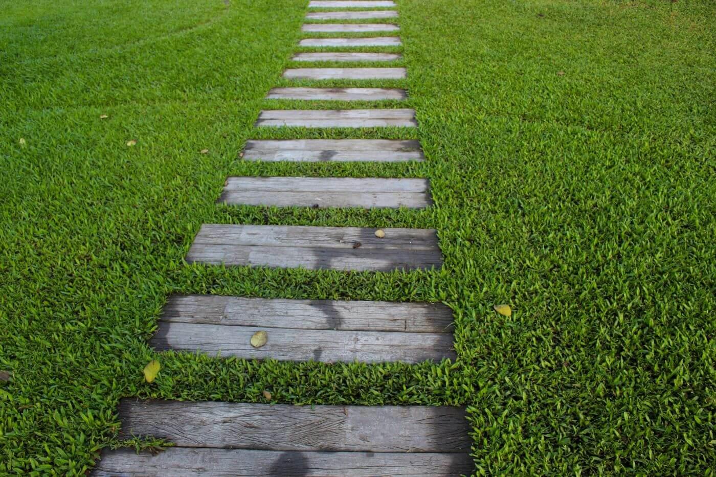 Holzschwellen in Paaren in einem grossen, grünen Garten als Symbol unserer Lebensreise