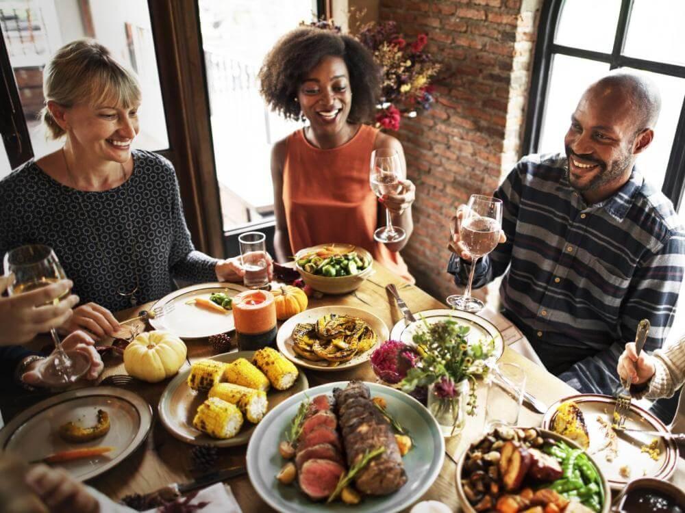 Vergnügte Personen, die in den USA das Erntedankfest-Mahl geniessen.